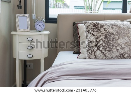 modern bedroom design with bed, pillows and lamp on table