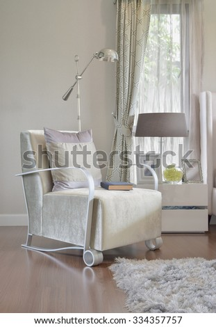 modern bedroom interior with gray pillow on armchair and bedside table lamp at home #334357757