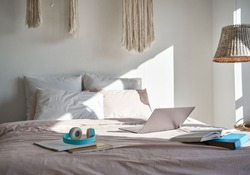 Modern bedroom interior with laptop computer, headphones, books on cozy bed in sunny room. Cosy hygge comfortable bed with technology student freelancer workspace at home indoors in morning light.