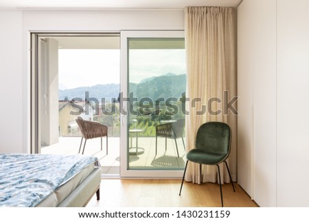 Modern bedroom with bed and velvet chair. Window overlooking nature. Nobody inside.