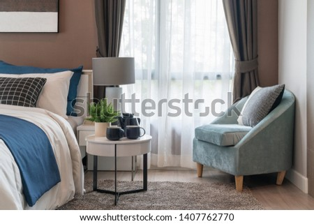 modern bedroom with modern lamp on table side and set of pillows on bed, interior design concept decoration