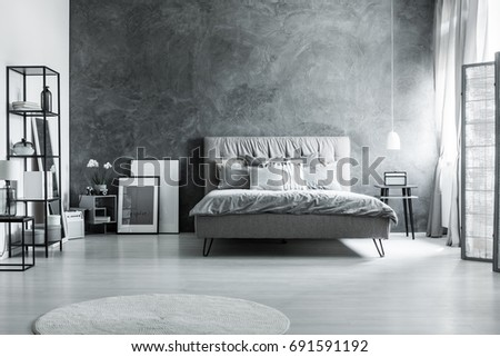 Modern bedroom with simple furniture, gray bedding and soft headboard #691591192