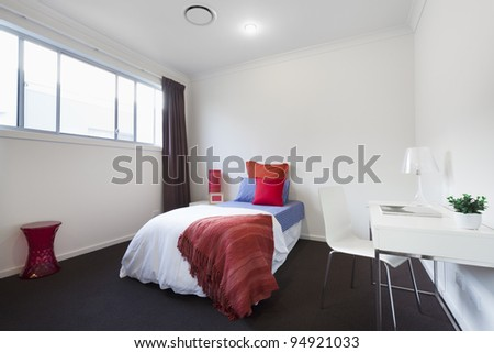 Modern bedroom with single bed, table and chair
