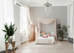 Modern bedroom with tester bed with pale pink tester and pale pink folding-screen, small accent pillows on the bed, minimalistic Scandinavian design bedroom with indoor plants and light grey walls.
