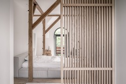 Modern bedroom with white walls, parquet, wooden beams and a lattice partition. There is a gray bed with light linens, doors to a balcony, wood chests with a statuette, hanging filament lamps.