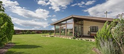 Modern beige country house with panoramic windows and green lawn in beautiful garden.