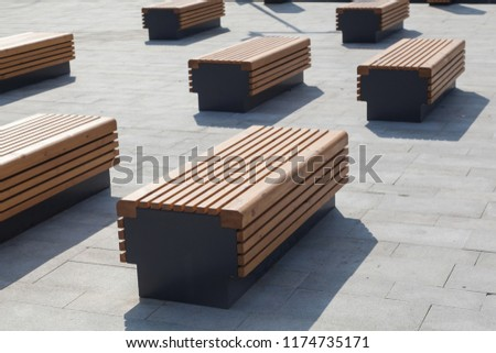 Modern benches in the city square on a sunny day. City improvement, urban planning, public spaces.
