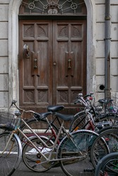 modern bicycles stand near an old stone building on the background of an arched wooden door