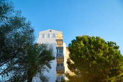 Modern big building, tree and greenery on foreground and blue sky on background. Hotel of block of flats is surrounded by green trees in summer. The concept of nice summer day in Turkey