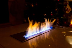Modern bio fireplace in the marble slab in the apartment decorated for Christmas