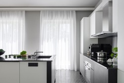 Modern black and white kitchen with big windows behind white curtains and with black and white kitchen island with sink