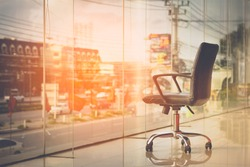 modern black chair in empty office space with large window, vintage picture style process,copy space.