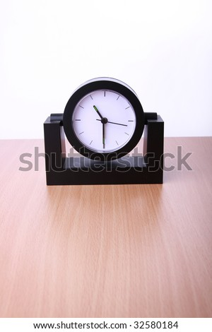 Modern black clock on table in the office. White background.
