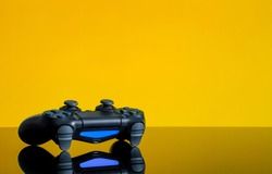 Modern black gamepad on a yellow background. Joystick black color on a smooth reflective table. Gaming concept