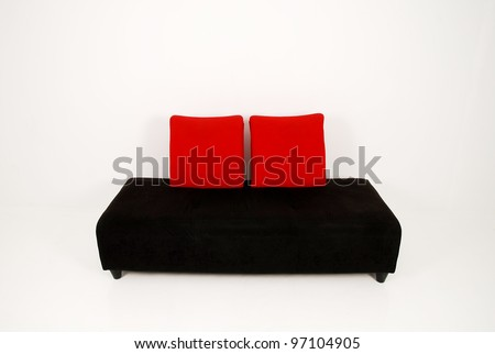 modern black sofa with red pillows isolated on a white background