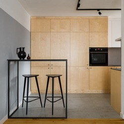 Modern, black table with tall bar stools in stylish kitchen with birch plywood cupboards