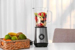 Modern blender and ingredients for healthy smoothie on kitchen table