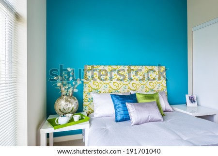 Modern blue bedroom interior with blue green and violet designer pillows in a luxury house Interior design