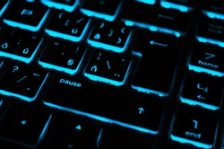 Modern blue iluminated backlit keyboard. Blue backlight, backlit on laptop or keyborad computer of gaming in the dark. Paused game. Cyber Attack, hacking and Internet security concept.