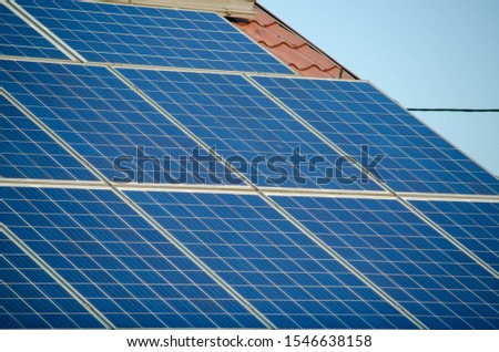 Modern blue photovoltaic solar panels on a roof, detail on a solar panels, solar panels on a house during sunny day in a city.