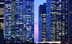 modern blue skyscrapers,  buildings, financial district and skyline by night with windows and office illuminated in Singapore