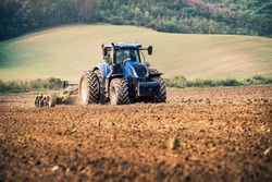 Modern blue tractor on the field during stubble-tillage cultivation after harvest with yellow equipment using GPS for precision farming in the fields of Czech Republic during sunny autumn day.