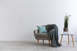 Modern boho cozy corner of home in living room. Gray vintage armchair with blue pillow and blanket, table with green plant in pot, wooden floor, on light wall background, copy space, mockup, nobody