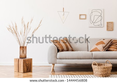 Modern boho interior of living room at cozy apartment with gray sofa, honey yellow pillows and plaid, mock up paintings, rattan basket and design personal accessories. Stylish home decor. Template. Photo stock ©