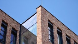 Modern brick and glass facade of the office building.  A contrasting combination of sky and brick texture on a building. Architectural facade of a red brick building..