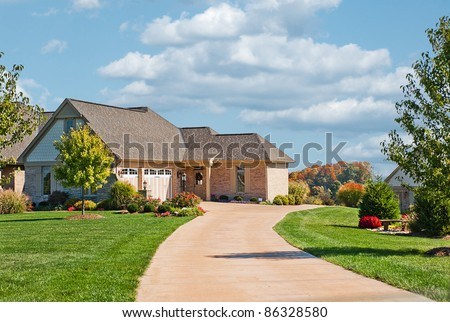 Modern brick, stone and shakes two story house in USA with a concrete driveway leading to a side entry garage in autumn.