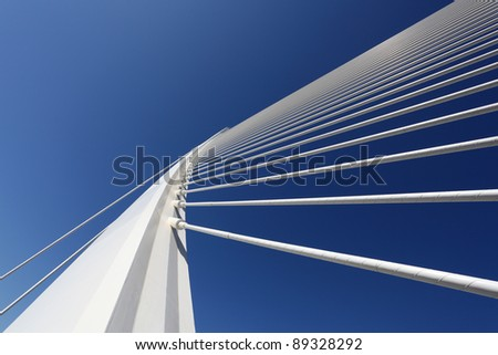 Modern bridge pylon against a blue sky #89328292