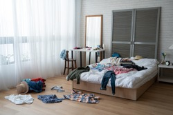 modern bright bedroom with messy clothes scatter on white bed and floor. empty room with nobody in cozy apartment. packing luggage suitcase for summer vacation and spring holidays concept lifestyle.