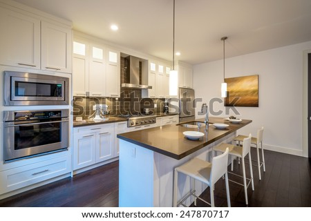 Modern, bright, clean, kitchen interior with stainless steel appliances in a luxury house.