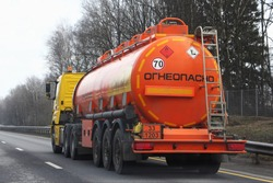 Modern bright orange semi truck fuel tanker with 33 1203 dangerous class sign and Russian inscription FLAMMABLE drive on highway at spring day in perspective, rear side view - ADR hazardous cargo
