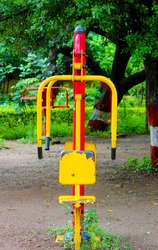 modern bright orange yellow gym equipment grass lawn park wear safety surfacing around base houses shrubs-trees in the background maharashtra India