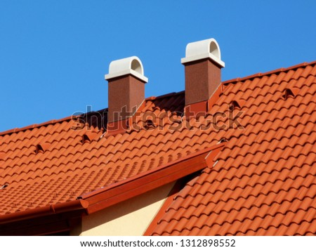 modern brown stucco finished chimneys with white ceramic cap stone, bright brown red clay tile roof tiles & clay vents under clear blue sky on crisp winter day in bright sunlight. construction concept #1312898552