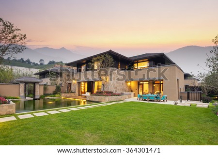 modern building by the fishpond and beautiful meadow in colorful sky at twilight