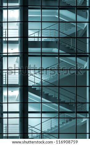 Modern building facade with staircase behind a transparent glass wall