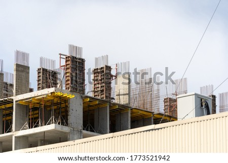 Modern building under construction with reinforcement formwork and on concrete wall, against blue copy space sky. Investment at housing development concept