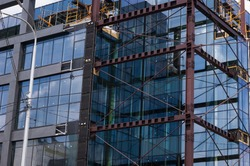 Modern building with curtain glass facades in the final stages of construction, facade metal x braces supportive structures