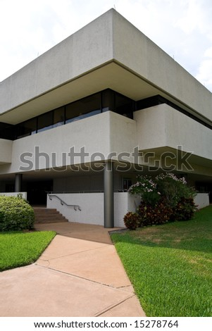 Modern building with sidewalk leading up to small staircase