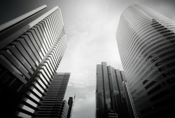Modern building with sun flare at Bangkok City, Thailand. Bottom view of Modern business skyscrapers. Concepts of banking, financial, economics, future. Monochrome black and white color.