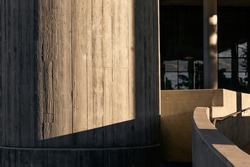 Modern building with textured column bathed in afternoon light.