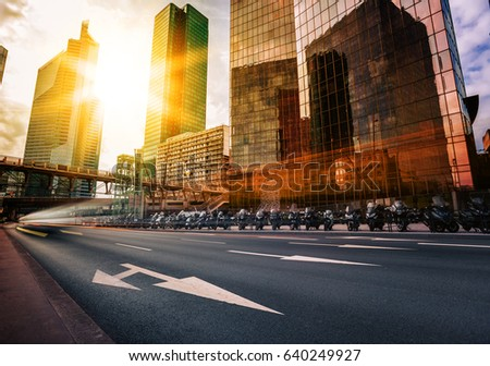 Modern buildings in Paris business district La Defense. Glass facade skyscrapers on a bright sunny day with sunbeams in the blue sky. Economics, finances, business activity and city traffic concept #640249927