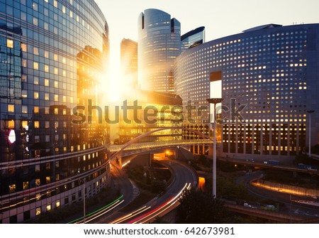 Modern buildings in Paris business district La Defense. Glass facade skyscrapers on a bright sunny day with sunbeams in the blue sky. Economics, finances, business activity and city traffic concept #642673981