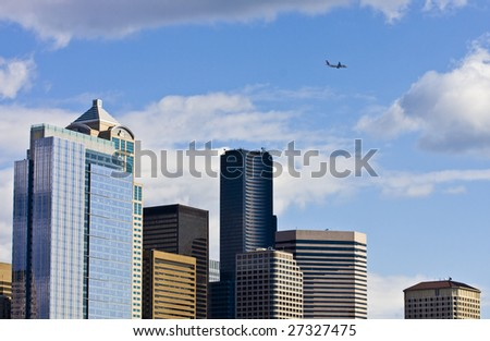 Modern Buildings of the Seattle Skyline with a jet airliner flying past
