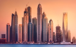 Modern buildings with gold reflection of sunset on Dubai Marina bay, UAE.