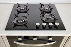 Modern built-in oven and gas stove classic design in dark tones under light stone marble or granite countertop in interior of contemporary kitchen.