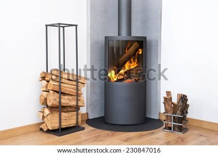 Modern burning stove next to a wood logs rack Stock fotó ©