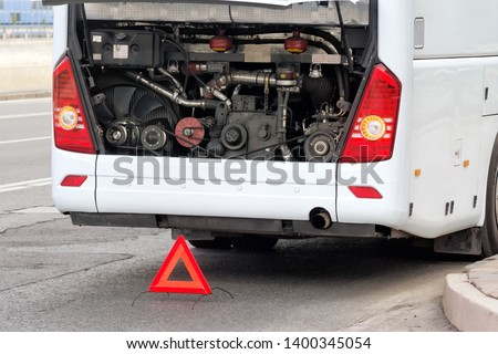 modern bus emergency stop for maintenance with open engine cover and triangle emergency sign on city street detailed closeup view of back side of white coach and motor bay interior travel concept #1400345054